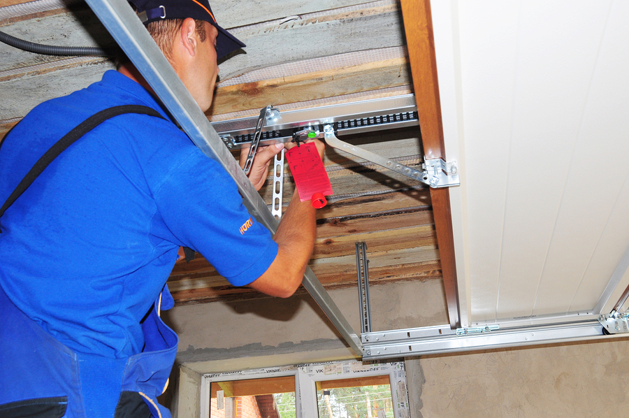 KYIV, UKRAINE - May, 14, 2018: Worker installing garage door opener system. Garage door repair.